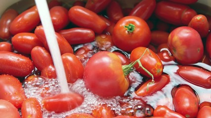 Washing fresh tomatoes under tap water from kitchen sink