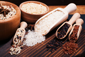 Different types of rice on a wooden background