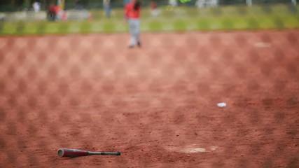A Baseball Bat Laying down in Baseball Field