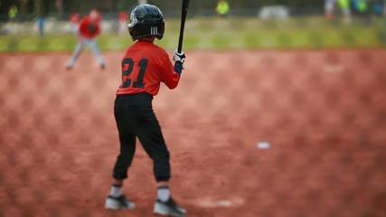 Kid Batting and Running at Baseball Game