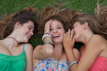 teen girls whispering and gossiping secrets