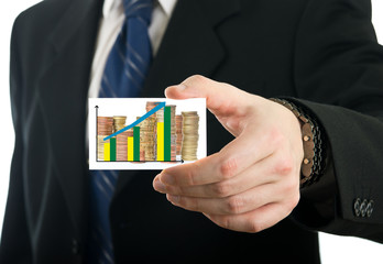 Businessman showing card with stack of coins