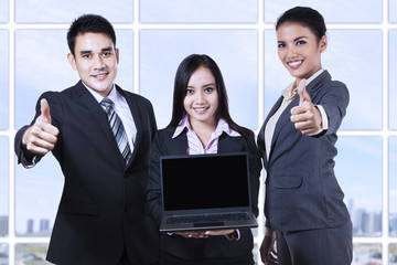 Asian business team showing blank screen on laptop