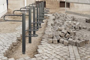 Montage neuer Fahrradständer in einer Fläche aus Pflastersteinen