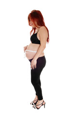 Pregnant woman measuring belly.