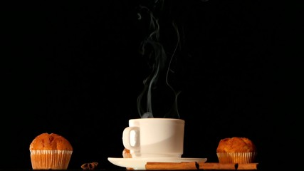 White steaming coffee cup with cakes, anise, cinnamon on black