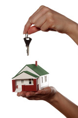 Miniature model house and key in woman's hands