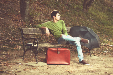 male sitting on a bench in the park