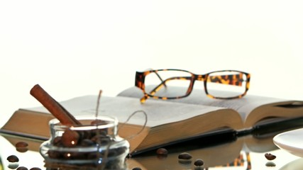 Cup of hot coffee and book with glasses, cinnamon, beans on