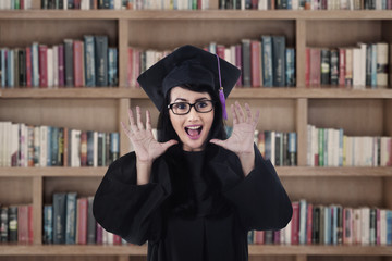 Excited female graduate shouting at library