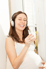 pregnant women drink a glass of milk and listening to music