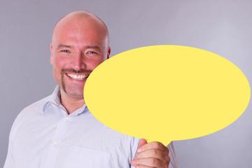 fröhlich lachender Mann mit einem Werbeschild in der Hand