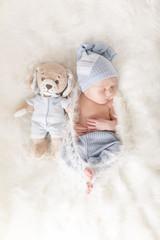 Newborn Baby mit süßem Outfit und Teddy von oben