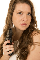 Woman with a serious expression pointing a black pistol