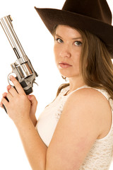 Cowgirl with revolver looking serious into the camera