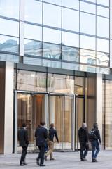 People walking past a modern building, zoom effect