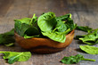 Spinach leaves in a wooden bowl. - 79412907