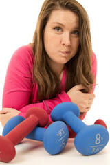Woman indifferent look about working out and barbells