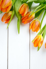 orange tulips on white wooden surface