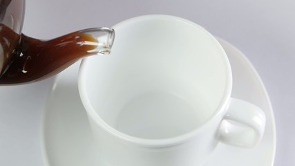 Coffee poured into a cup on white background, slow motion