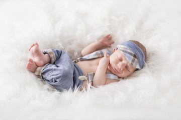 Newborn Kleiner Bub liegend mit süßem Outfit