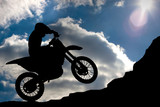 Fototapety Motocross - silhouette with a rock and blue sky with sun