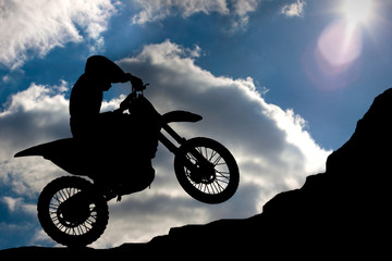 Motocross - silhouette with a rock and blue sky with sun