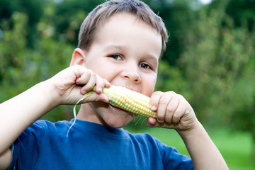 boy eating young corn outdoors
