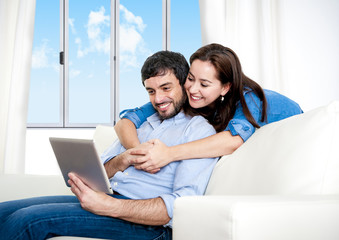 happy couple on home couch enjoying using digital tablet
