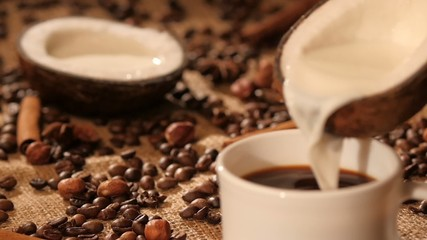 Pouring coconut milk into a cup with coffee, dynamic change of