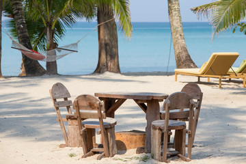 Wooden table and chairs of a beach tropical garden near the sea