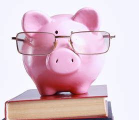 Piggy bank with glasses and bookin isolated white