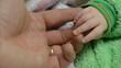Touching Newborn Baby's Hands
