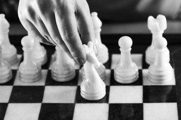 Hand with white knight on chessboard