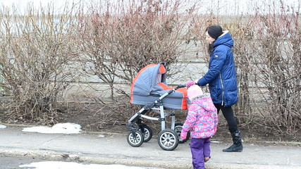 Mother with Daughter Walkin in Park with Newborn Child in  Baby