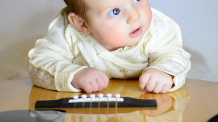 Newborn Baby Lying on Guitar. Motorized Dolly Shot