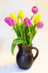 Bouquet of pink and yellow tulips in an old clay pot isolated