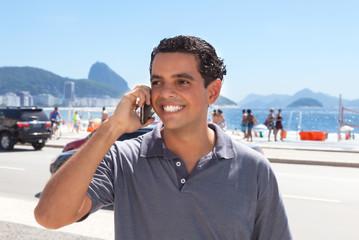 Lachender junger Mann telefoniert in Rio de Janeiro
