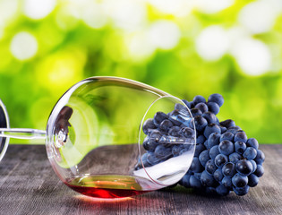 Bunch of grapes and glass of red wine lying on a black wooden ta