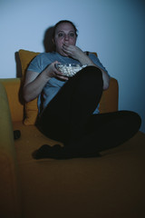 Overweight woman watching horror movie on TV