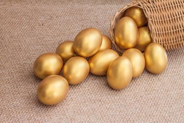 Heap of golden easter egg in wicker basket