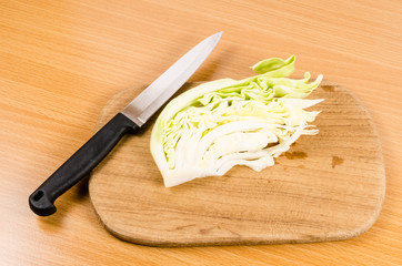 cabbage and knife on wooden board