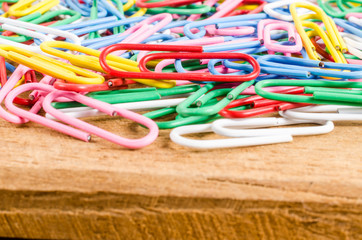 group of colorful paper clip on wooden board