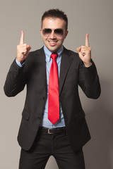 Haapy young business man holding two fingers up.