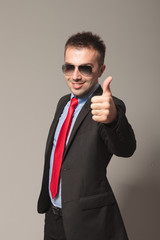 Handsome business man showing the thums up gesture.