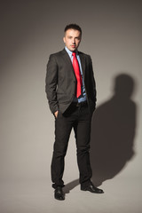 Attractive business man standing on studio background