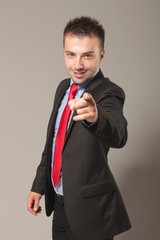 Young business man smiling while pointing at the camera.