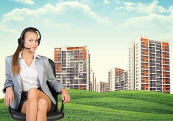 Woman in headphones sits on chair. Buildings, green hills as