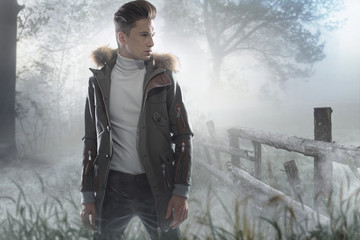 Young handsome man on the frozen meadow