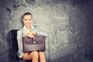 Woman wearing jacket, blouse holding briefcase. Background